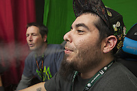 USA. Colorado state. Denver. Jesse Toks (R )works during the day at Medicine Man and plays internet video games at home in the evenings and weekends. Pete Williams (L), owner of Medicine Man, exhales marijuana smoke while watching the online gamer playing. Jesse Toks is exhaling smoke after dabbing which is a slang term used to describe taking single dose hash hits of concentrates that are referred to as oil, erl, earwax, wax, budder, BHO or shatter using pipes and bongs that are made specifically for smoking these cannabis extracts. Medicine Man began nearly six years ago as a small medical marijuana operation and has since grown to be the largest single marijuana dispensary, both recreational and medical, in the state of Colorado and has aspirations of becoming a national brand if pot legalization continues its march. Cannabis, commonly known as marijuana, is a preparation of the Cannabis plant intended for use as a psychoactive drug and as medicine. Pharmacologically, the principal psychoactive constituent of cannabis is tetrahydrocannabinol (THC); it is one of 483 known compounds in the plant, including at least 84 other cannabinoids, such as cannabidiol (CBD), cannabinol (CBN), tetrahydrocannabivarin (THCV), and cannabigerol (CBG). 18.12.2014 © 2014 Didier Ruef