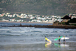 Africa, South Africa, Muizenberg.  Surfers at Muizenberg Beach on the Cape peninsula, near Cape Town.