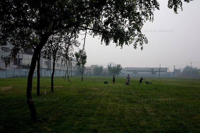 City workers mow a vacant lot in Beijing, China on Monday, August 4, 2008. Two months ago, neighbors say the lot was home to several poor people living in shack-like houses.  The city of Beijing is gearing up for the opening ceremonies of the Olympic Games.  Kevin German