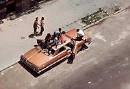 Bronx, New York City, NY - Summer of 1966 <br /> On Fox Street in the Bronx, an abandoned car becomes a jungle gym for kids to play in and on. <br /> Bronx, New York City, NY. Et&eacute; 1966.<br /> Les voitures abandonn&eacute;es deviennent la terrain de jeux des enfants en attendant que la fourri&egrave;re passe ramasser l&rsquo;&eacute;pave, ce qui peut prendre des semaines.