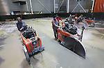 Foto: VidiPhoto<br /> <br /> NIJMEGEN - Met een gezamenlijk vermogen van 350 pk ploegen vijf zware vloerzagen van Husqvarna dwars door de toplaag van een 60 cm dikke, zwaargewapende betonvloer van Royal Smit Transformers in Nijmegen. Door slijtage voldoet de ondergrond van de testhal nu niet meer en wordt deze razendsnel vernieuwd om luchtkussentransport van de megazware transformatoren weer mogelijk te maken. Vanwege de dikte van het beton en de zware wapening koos betonzaagbedrijf WIHA BV uit Dinxperlo voor de op dit moment meest geavanceerde diamantzaagmachines met emissiearme dieselmotoren. In maximaal 12 uur tijd dient 800 meter betonvloer op een diepte van 20 cm doorgezaagd te worden. Na het afvoeren van het puin krijgt de vloer een nieuwe bovenlaag van 20 cm dikte.  Op 5 januari 2015 is de testhal voor transformatoren weer gereed voor gebruik. Het is voor zover bekend voor het eerst dat vijf zware vloerzagen tegelijk worden ingezet. rden ingezet.