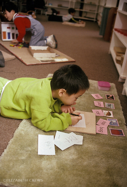 Palo Alto CA Boy, age four, studying words and writing letters at Montessori preschool