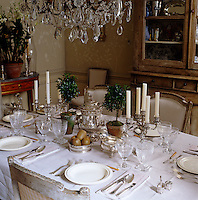 Close up of a laid table dressed in white crisp table linens and adorned with silverware