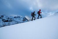Two hikers in winter hiking towards Hustind mountain peak, Flakstadøy, Lofoten Islands, Norway