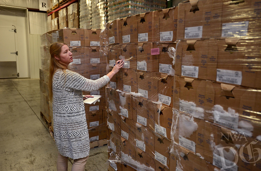 NWA Democrat-Gazette/BEN GOFF @NWABENGOFF<br /> Trish Dossett, reciever at Northwest Arkansas Food Bank, inspects palets of chicken on Monday Dec. 19, 2016 at Northwest Arkansas Food Bank in Bethel Heights. Harps and Smart Chicken partnered to donate 5,300 pounds of chicken to the food bank through their 'Smart Giving' annual program, which is in it's 13th year.