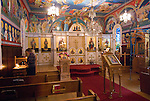 Liturgy service at St. Sava Orthodox Church, Jackson, Calif...Betsy Tumbas lights a candle by the altar before the liturgy service conducted by the Very Reverend Stavrofor Miladin Garich, Father Stephen Tumbas assisted by Dan Stojanovich.