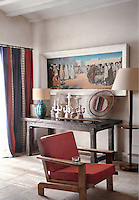 A corner of the living room is furnished with a rustic table on which is displayed a collection of ceramic sculptures and other objects