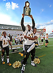 Heritage offensive lineman Tedarrell Slaton and quarterback Torrance Gibson celebrate with the state championship trophy as American Heritage defeats Green Cove Springs Clay in the Class 5A FHSAA state football championship 66-8 in Orlando on Friday, December 13, 2013.