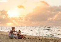 A family enjoys the beach at sunset, Waialua Beach, O'ahu.