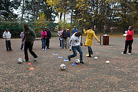 12 May 2011, Leribe, Leribe District, Lesotho. Kick4Life is a sports-based programme aimed at educating children between 12-19 on issues around HIV/AIDS, gender and other life skills. Youths meet out of school at the youth centre and discuss issues of relevance to them and using ballplay to demonstrate wome of the issues they deal with. Coordinator Mpho Mabea (striped sweater); Coach Malikhetla Motselebane (red t-shirt) and Mailinyane Lihaba (pink shirt) work with the youth trough this progamme.