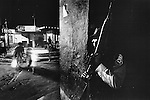 A Salvadoran soldier keeps watch from a darkened doorway as people scatter following an explosion nearby.