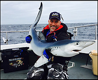 BNPS.co.uk (01202 558833)<br /> Pic: JayOxenham/BNPS<br /> <br /> Jay with a smaller shark which he caught on seperate trip.<br /> <br /> When the shark bites...<br /> <br /> A Frank Sinatra impersonator stares down the 'pearly white' teeth of a monster 450lb shark he caught on a fishing trip of the coast of Cornwall.<br /> <br /> The enormous porbeagle shark, that is related to the deadly Great White, was caught one mile from shore by professional swing singer Jay Oxenham.<br /> <br /> Jay, 46, who performs all over Europe, spent almost two hours tussling with the gigantic 8ft long shark which was 'as wide as a cow' after it went for his mackerel bait.<br /> <br /> Weighing over 30st, the shark was far too big to lift on board the boat Jay was on so all he could do was bring it alongside to measure and photograph it - including the obligatory selfie - before releasing it safe and well.