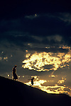 Silhouetted mother and daughter along a hillside at sunset with storm clouds in the background Gas Works Park Lake union Seattle Washington State USA