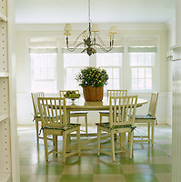 A round dining table and set of white chairs stand on a painted green and white chequered wooden floor