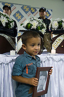 A boy holds a picture in honor of one of the nine skeletal presented to their families by The Attorney General's Office in Medellin,. The exhumations Were Conducted in the Departments of Antioquia, Risaralda and Meta., Colombia, 20/04/2012. Photo by Fredy Amariles / viewpress.