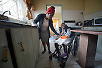 Tendai Nyamkondiwa accompanies her niece, Ngonidzashe Rondozai, in the kitchen of their house in Harare, Zimbabwe.  Rondozai, 17, has cerebral palsy, and Nyamkondiwa, her aunt, is her primary caregiver. Rondozai uses an appropriately designed and fitted wheelchair provided by the Jairos Jiri Association with support from CBM-US.