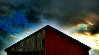 Red siding on old barn with stormy sky. iPhone photo. Manipulated with app.