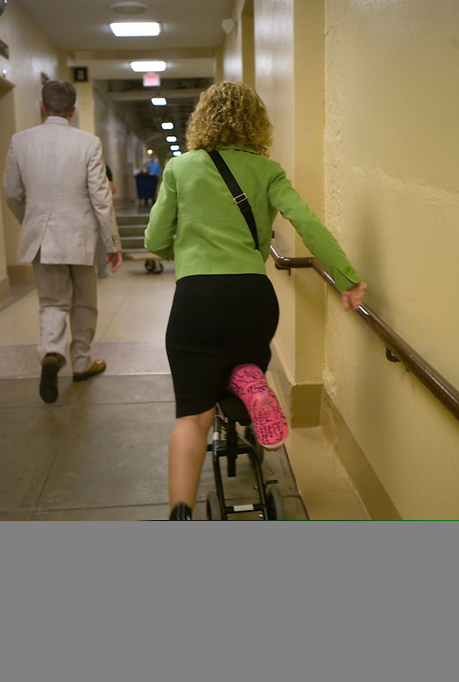 WASHINGTON, DC - July 30: Rep. Debbie Wasserman Schultz, D-Fla., pushes her way, scooter-style, up a ramp in the U.S. Capitol basement on her way to the House chamber for a series of votes. She sprained her ankle and broke her leg Congressional Women's Softball Game July 15 sliding into second. With her is spokesman Jonathan Beeton. (Photo by Scott J. Ferrell/Congressional Quarterly)
