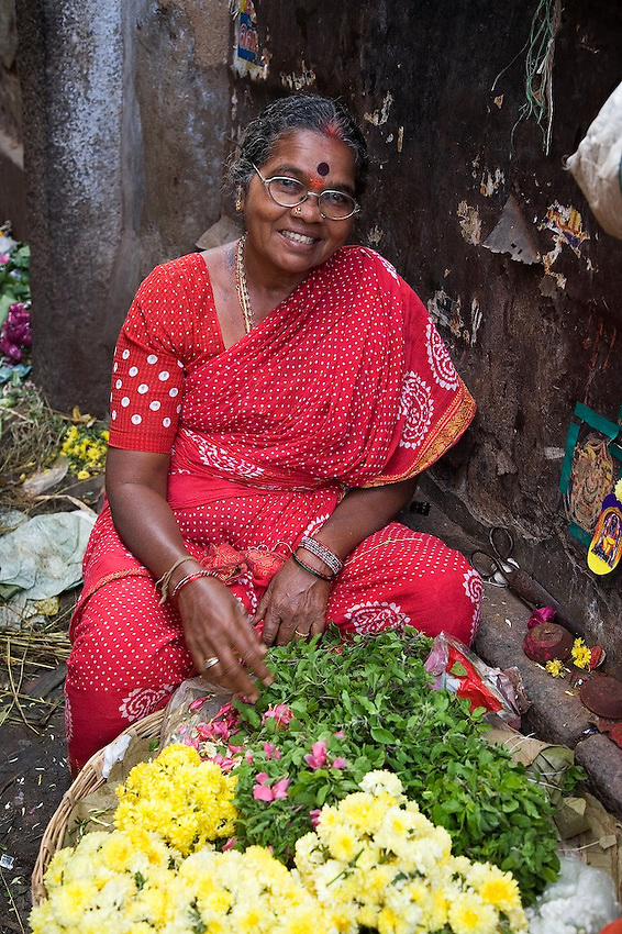 Lady in red sari sells flowers in southern Indian market