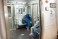 A homeless individual sleeps on the subway in New York on Sunday, October 2, 2016. (© Richard B. Levine)