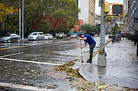A man cleaning storm debris from the high winds of Hurricane Sandy away from a storm drain seen in the New York neighborhood of Chelsea on Tuesday, October 30, 2012. Hurricane Sandy roared into New York disrupting the transit system and causing widespread power outages. Con Edison is estimating it will take four days to get electricity back to Lower Manhattan. (© Frances M. Roberts)