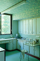 This 50s style kitchen has pale blue units and a ceiling covered in patterned paper