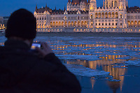 Man photographs ice blocks floating on the surface of river Danube in front of the houses of the Parliament in Budapest, Hungary on January 08, 2017. ATTILA VOLGYI