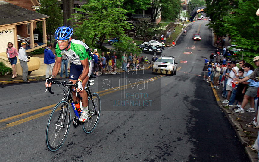 Alejandro Acton, of Target Training, climbs Clocktower Hill during Stage 2 of the 2006 Ford Tour de Georgia as the broom wagon follows. Acton spent about 100 miles on a solo breakaway before being caught by the main pack.<br />