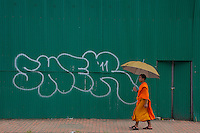 A Buddhist Monk with his Umbrella in stark contrast against a construction site green wall. Luang Prabang