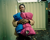 """28 year old Anwar, from the Darfur region of Sudan, collects sleeping bags at a drop-in centre for asylum seekers in North London. He claimed asylum in 2004 after escaping from the ethnic violence in Darfur and spent time destitute, surviving on the kindnss of friends, until 2008 when he was granted leave to remain in the UK. He is overjoyed to be safe but is still struggling to survive and has not managed to find any accommodation. """"I'm sleeping rough and it has caused my feet to swell. My GP is trying to help me get accommodation."""".."""