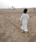 A boy watched a United Nations helicopter, which transports aid workers throughout Sudan's Darfur region, which has been plagued by violent conflict between government forces, Arab militias, and rebel soldiers.