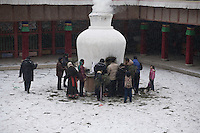 Some pilgrims are burning juniper in the courtyard of the Great Assembly Hall of the monastery of Labrang to honnor Tsongkhapa, the founder of the Gelukpa order and to improve their future life.