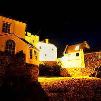Cottages lit up at night by the beach in St Ives, Cornwall..
