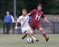 Boston College midfielder Brendan Hayes (29) controls the ball as Harvard University defender Tyler Evans (3) closes.Boston College (white) defeated Harvard University (crimson), 3-2, at Newton Campus Field, on October 22, 2013.