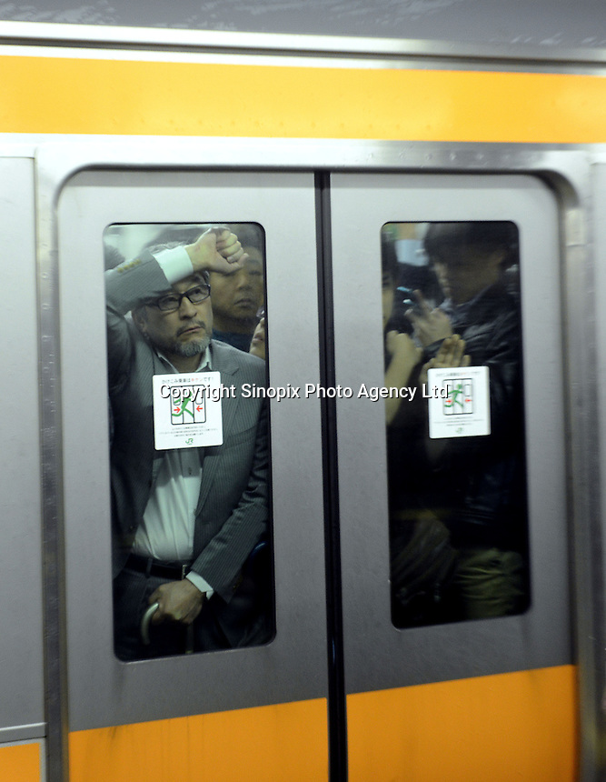 Businessmen looks through the window of a packed train in Shinjuku Station, Tokyo, Japan duringrush-hour. With up to 4 million passengers passing through it every day, Shinjuku station, Tokyo, Japan, is the busiest train station in the world. The station was used by an average of 3.64 million people per day.  That&rsquo;s 1.3 billion a year.  Or a fifth of humanity. Shinjuku has 36 platforms, and connects 12 different subway and railway lines.  Morning rush hour is pandemonium with all trains 200% full. <br /> <br /> Photo by Richard jones / sinopix