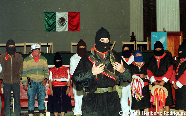 Zapatista Subcomandante Marcos talks with media during the beginning of the peace talks between Mexican government envoys and Zapatista comandantes at the San Cristobal Las Casas' Cathedral, February 21, 1994. Commander David, Comandante Ramona look on, among others Zapatista comandantes. The Zapatista National Liberation Army (EZLN) launched an uprising in January 1st, 1994 demanding Indian rights and opposing to the North American Free Trade Agrreement (NAFTA) signed by Carlos Salinas de Gortari with US and Canada governments. Photo by Heriberto Rodriguez