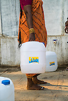 A woman waits to buy safe water from the iJal station in Peddapur, a remote village in Warangal, Telangana, India, on 22nd March 2015. Safe Water Network works with local communities that live beyond the water pipeline to establish sustainable and reliable water treatment stations within their villages to provide potable and safe water to the communities at a nominal cost. Photo by Suzanne Lee/Panos Pictures for Safe Water Network