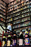 A customer looks at some of the hundreds of bottles of awamori and habushu that line shelves of specialist awamori store Awamori Gura in Naha, Okinawa Prefecture, Japan, on May 20, 2012. Photographer: Robert Gilhooly