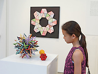 Surface to Structure origami exhibition at Cooper Union, New York. Gallery view. Event Horizon (left) designed and folded by Byriah Loper 2013. Little Roses Kusudama designed and folded by Maria Sinayskaya 2011 (red front). Star Icosahedron designed and folded by Evan Zodl 2012 (yellow back).