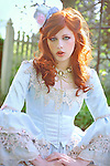 A pretty girl with red hair outdoors in a Victorian white dress in front of a fence wearing pearls and a small top hat