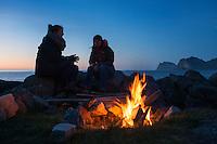 Two female travelers sitting around campfire near beach, Storsandnes, Flakstadøy, Lofoten Islands, Norway