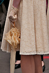A woman wears an eyelet dress and carries a parasol to the Easter Parade in New York City on Fifth Avenue
