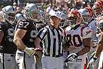Referee gets between Oakland Raiders defensive tackle John Parrella (97) and Cincinnati Bengals wide receiver Peter Warrick (80) on Sunday, September 14, 2003, in Oakland, California. The Raiders defeated the Bengals 23-20.