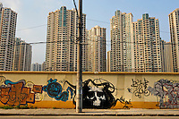 Death's head graffiti and new highrise apartment buildings.