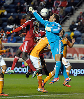 Houston goalkeeper Tally Hall (1) tries to punch away the ball as Chicago forward Dominic Oduro (8) goes for the header.  The Houston Dynamo defeated the Chicago Fire 2-1 in the Eastern Conference play-in game for the MLS Playoffs at Toyota Park in Bridgeview, IL on October 31, 2012.