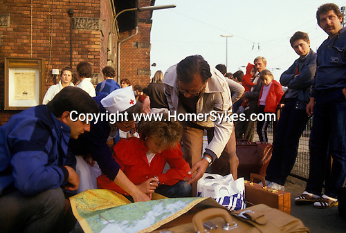 Friedland refugee camp West Germany. 1980's Polish refugees at the train station look at a map of Germany to see where they are heading for.