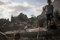 "In this Friday, Aug. 15, 2014 photo, Palestinian children stand over the rubble of their house as they look for their belongings after israeli airstrikes and artillery shelling hit Shuyaja neighborhood during the ""Protective Edge"" military operation in Gaza City. After a five days truce was declared on 13th August between Hamas and Israel, civilian population went back to what remains from their houses and goods in Gaza Strip. (Photo/Narciso Contreras)"