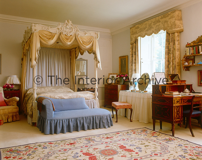 The bedroom is dominated by a carved four-poster bed with a bed cover and matching curtains in a toile de Jouy