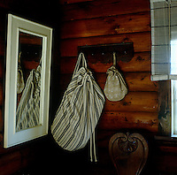 A striped linen duffle bag and a small embroidered linen bag hang on hooks on the wood-clad wall of this bedroom