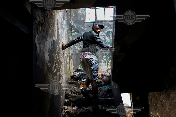 Simo on his way up to the roof a 'hijacked building' (slang that decribes an illegally occupied squat) where he lives in in Hillbrow. The building has neither electricity nor running water, and refuse is piled up outside the walls. Simo says he has been living here for 16 years.  Hillbrow, in downtown Johannesburg, is the city's most notorious neighbourhood. It is overcrowded, ridden with illegal squats and suffers from high levels of crime much of which is related the thriving illicit drug trade.
